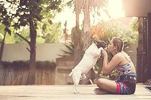 woman playing outside with her dog which is one of the best summer activities you can do with your dog