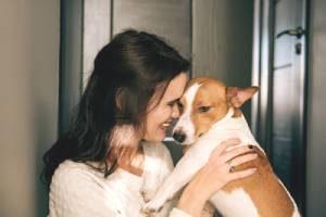 Dog sitter smiling while hugging a dog