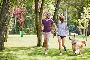 couple walking dog in secluded park to distract the dog barking at another dog