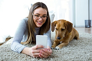 a woman with her dog using pet technology products