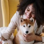Woman preventing pet separation anxiety in dog