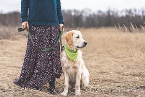 women walking her dog on a leash and green bandana