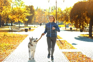 Happy,Young,Woman,Jogging,With,Her,Dog,In,Park