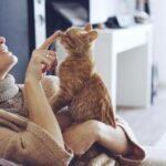young woman wearing warm sweater is resting with a cat